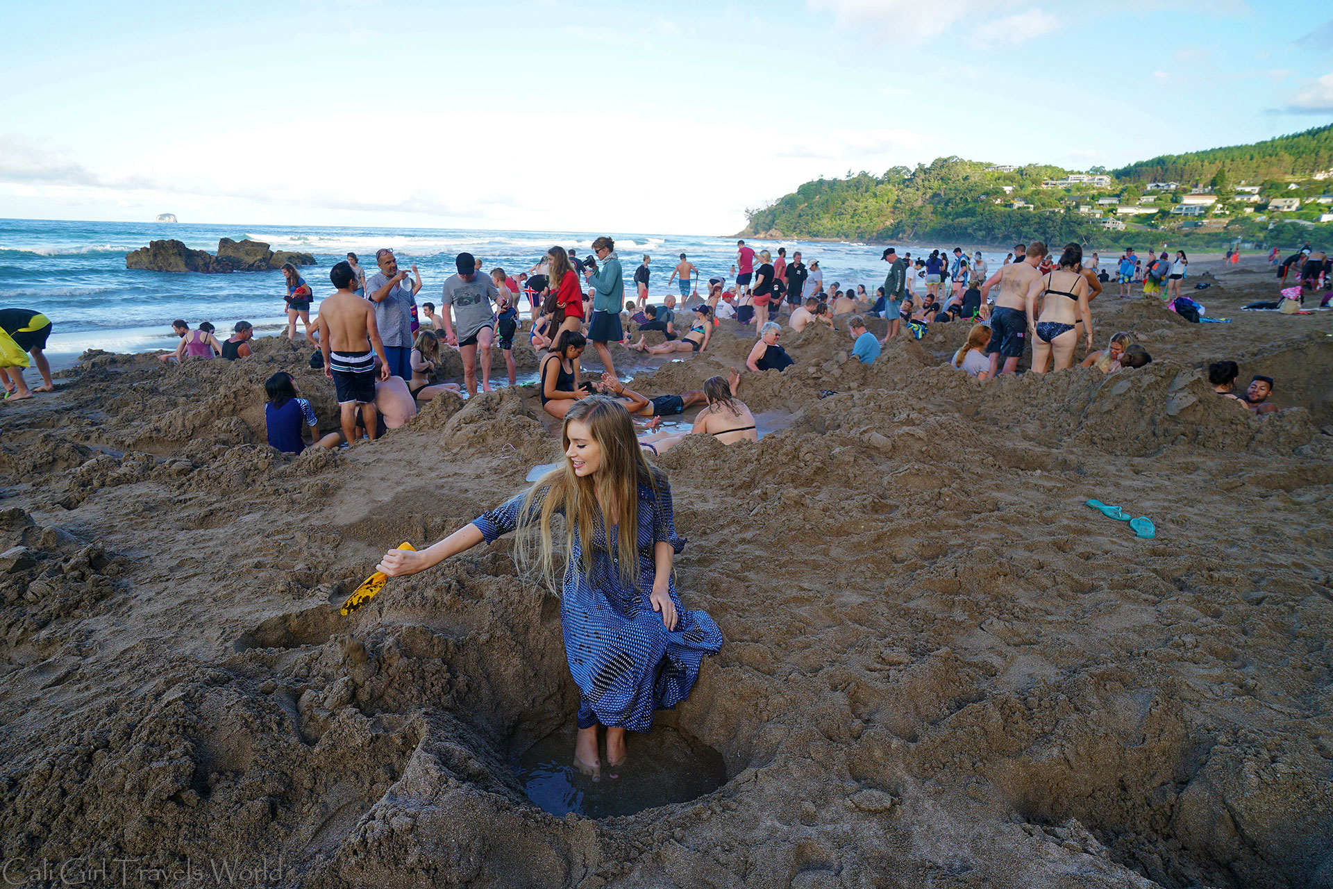 Female travel blogger soaks her feet in hot spring water at Hot Water Beach in the Coromandel, New Zealand