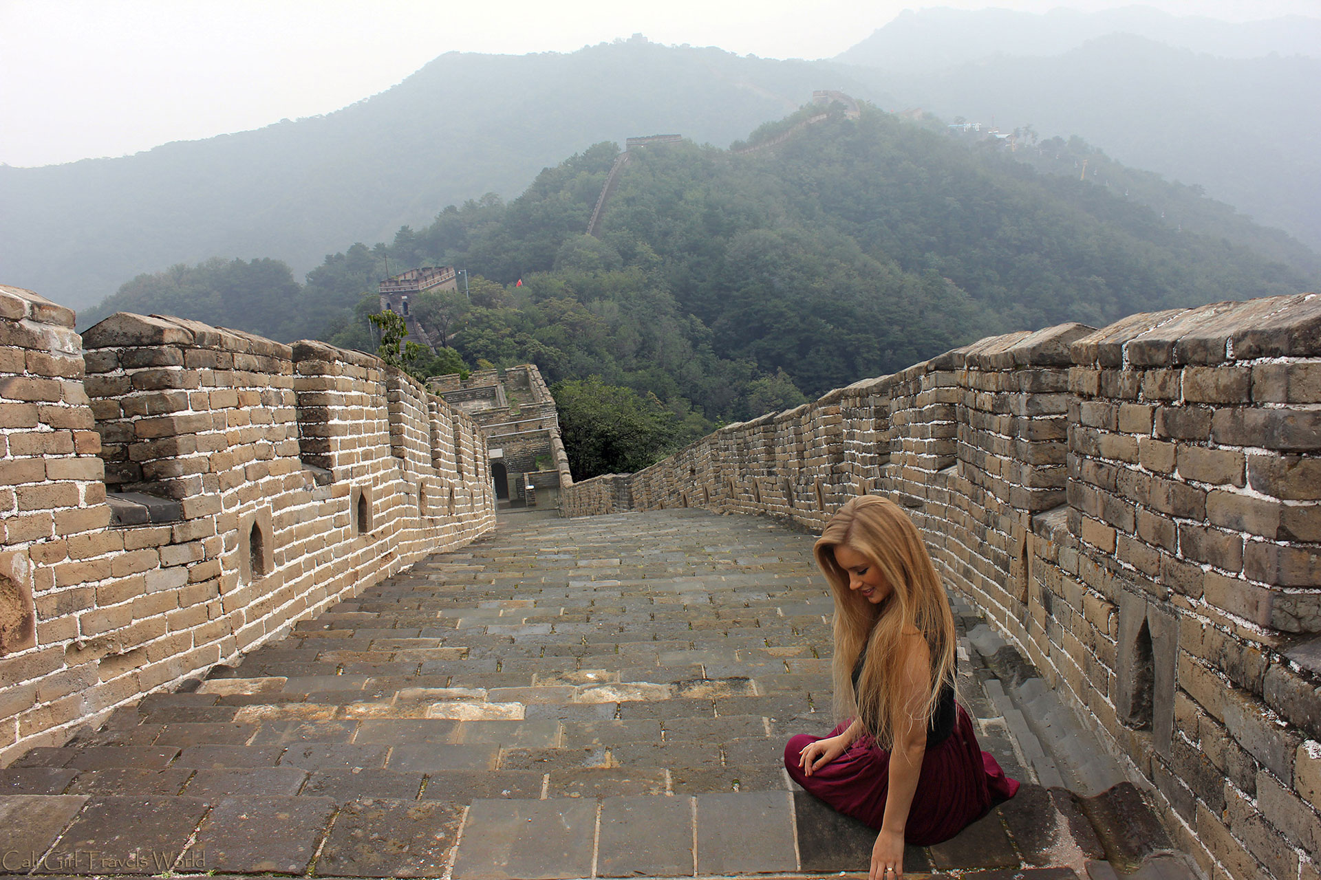 Female adventure blogger sitting at a peak of the Great Wall of China.