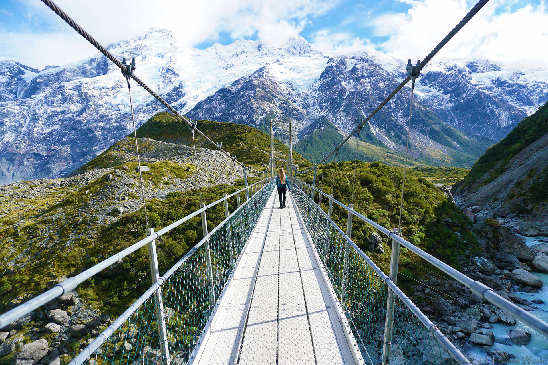 Female Travel blogger walking down suspension bridge on the Hooker Valley Track near glaciers at Mount Cook in South Island, New Zealand.