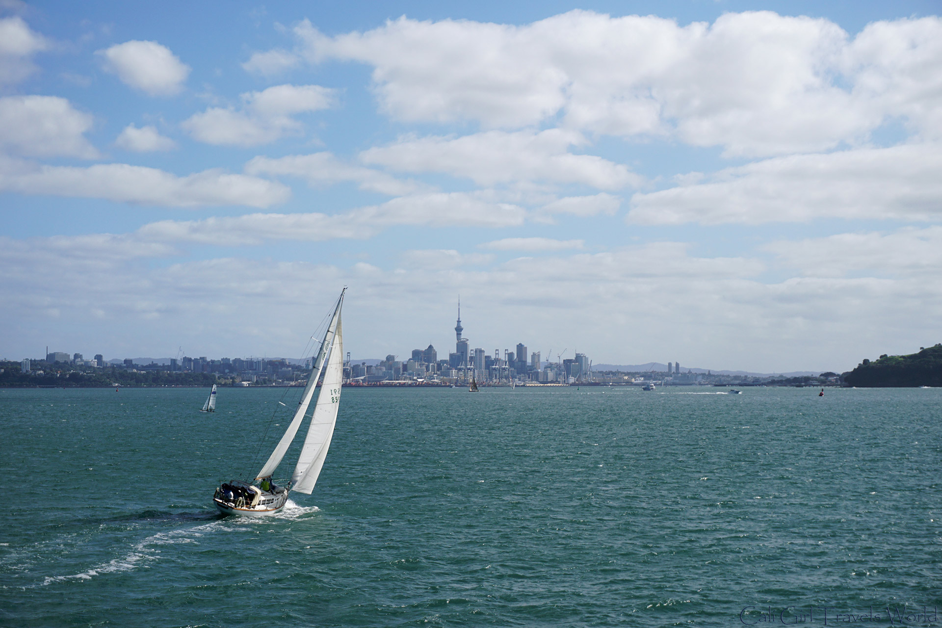 A view from our ship of Auckland city with a boat sailing in front, in the North Island of New Zealand.