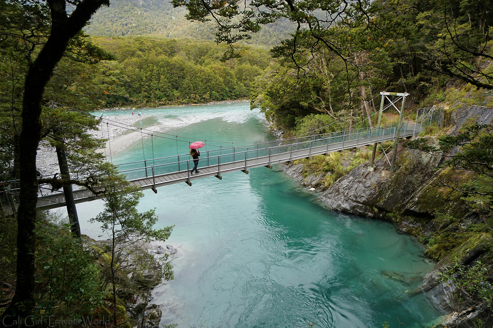 A female travel blogger walking over a suspension bridge above the clear blue pools near Wanaka and Haast in New Zealand.
