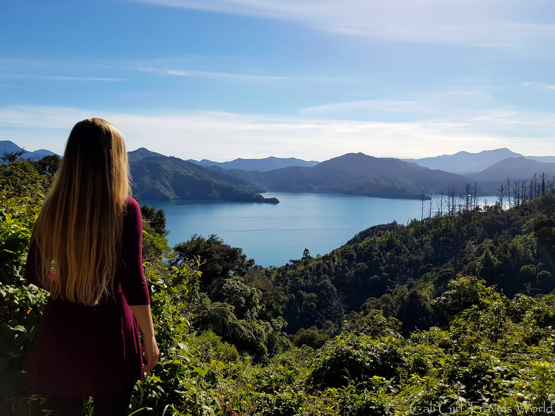 Blonde female travel blogger looking out to picton sound along queen charlotte drive in South Island, NZ