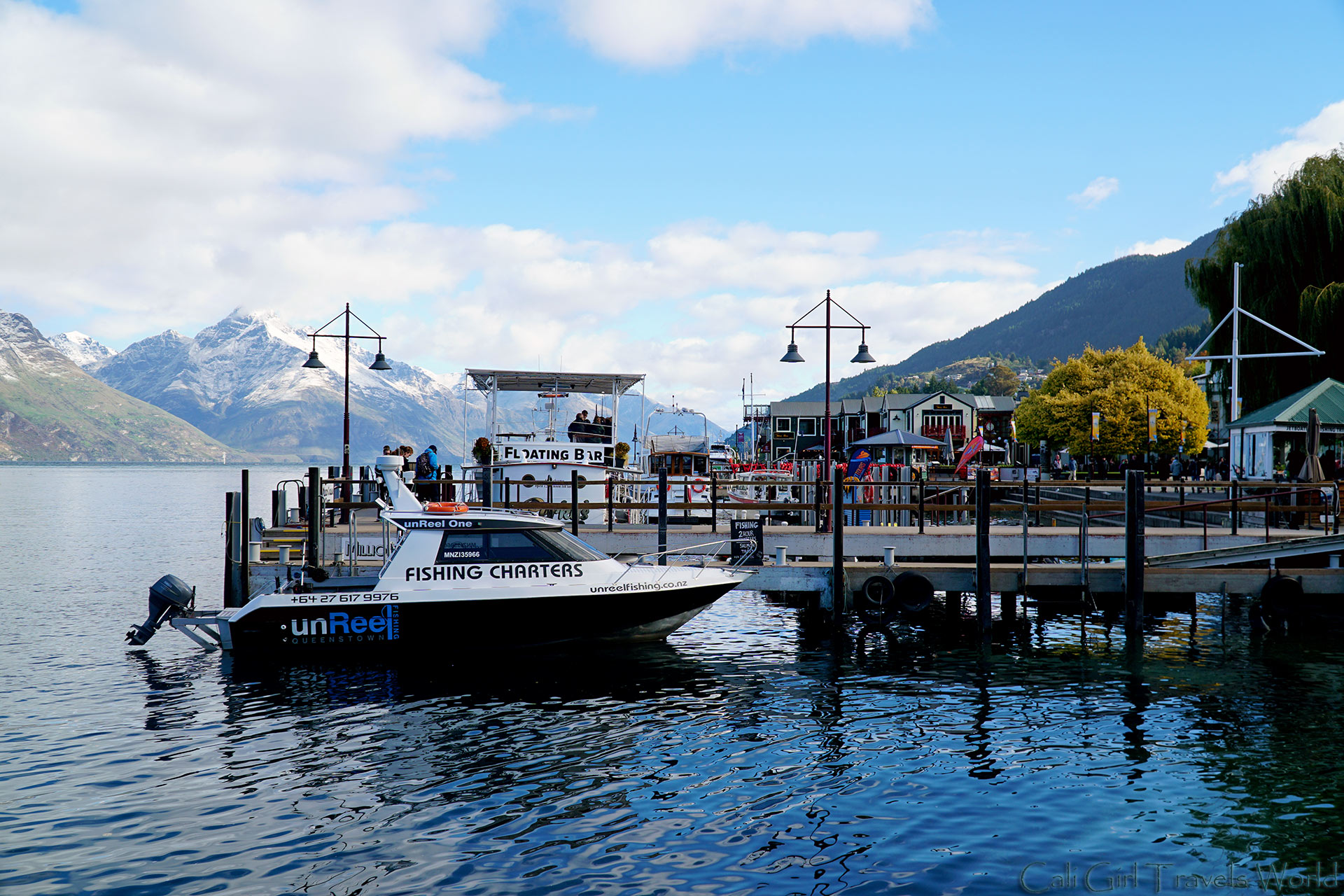 Looking out to downtown Queenstown waterfront, with boats and snow-capped mountains in the background in South Island, New Zealand.