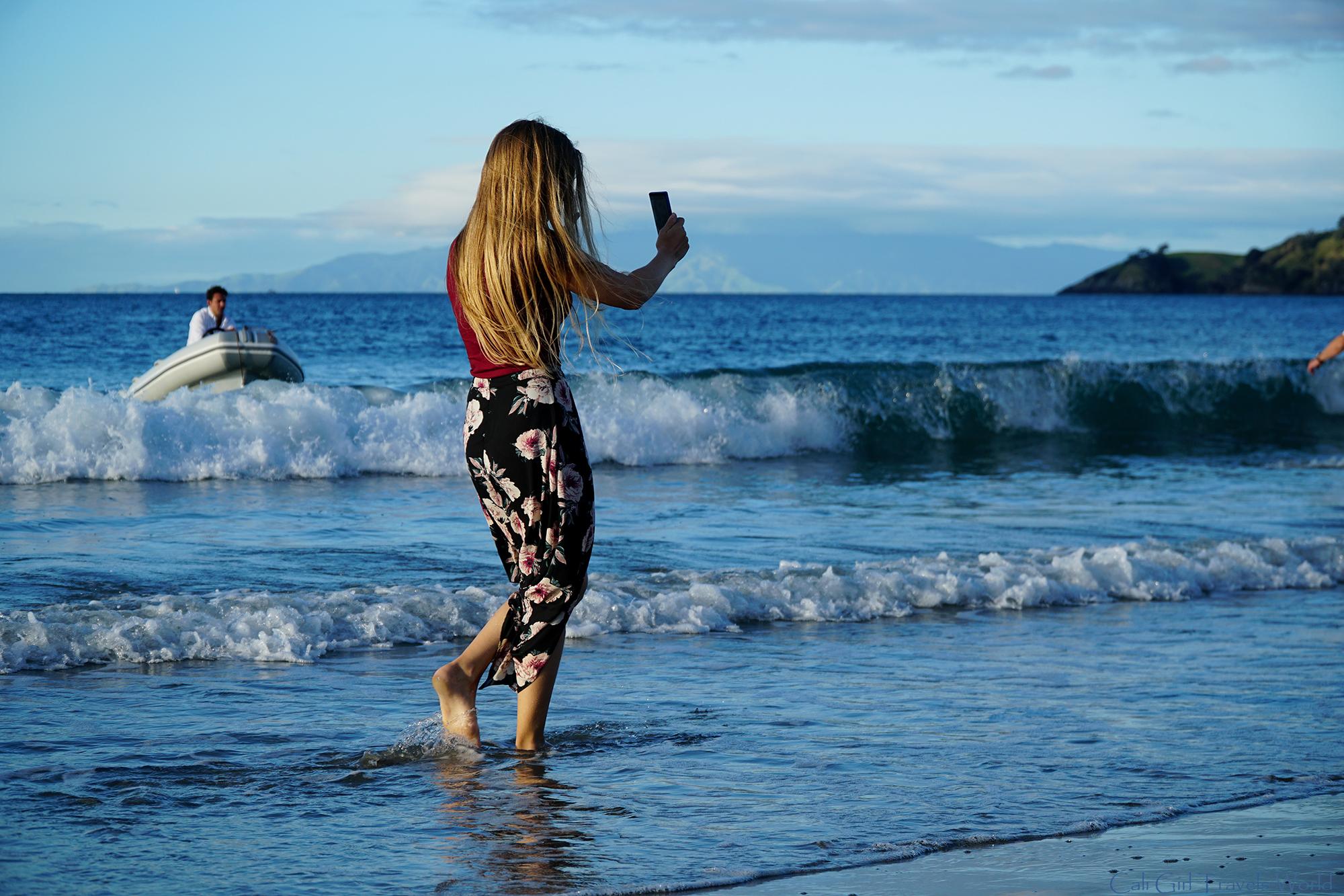 Female traveler walking along Onetangi beach on Waiheke island taking a photo with a smartphone.