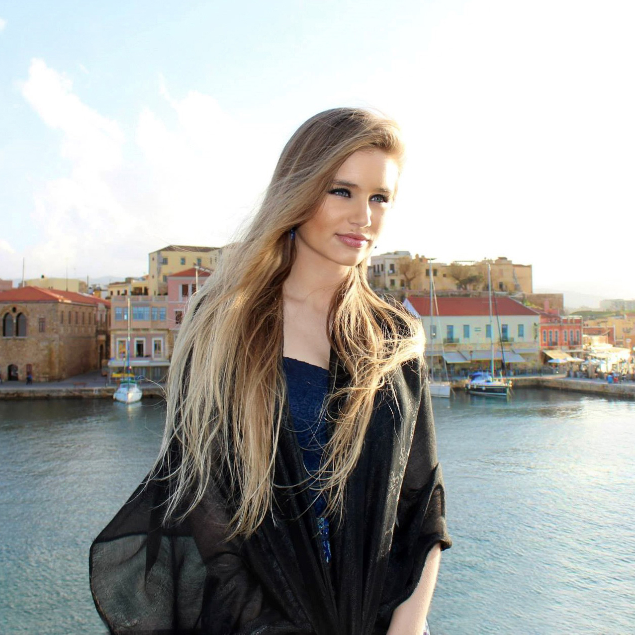 Female travel blogger in Chania, Greece admiring the view of the city.
