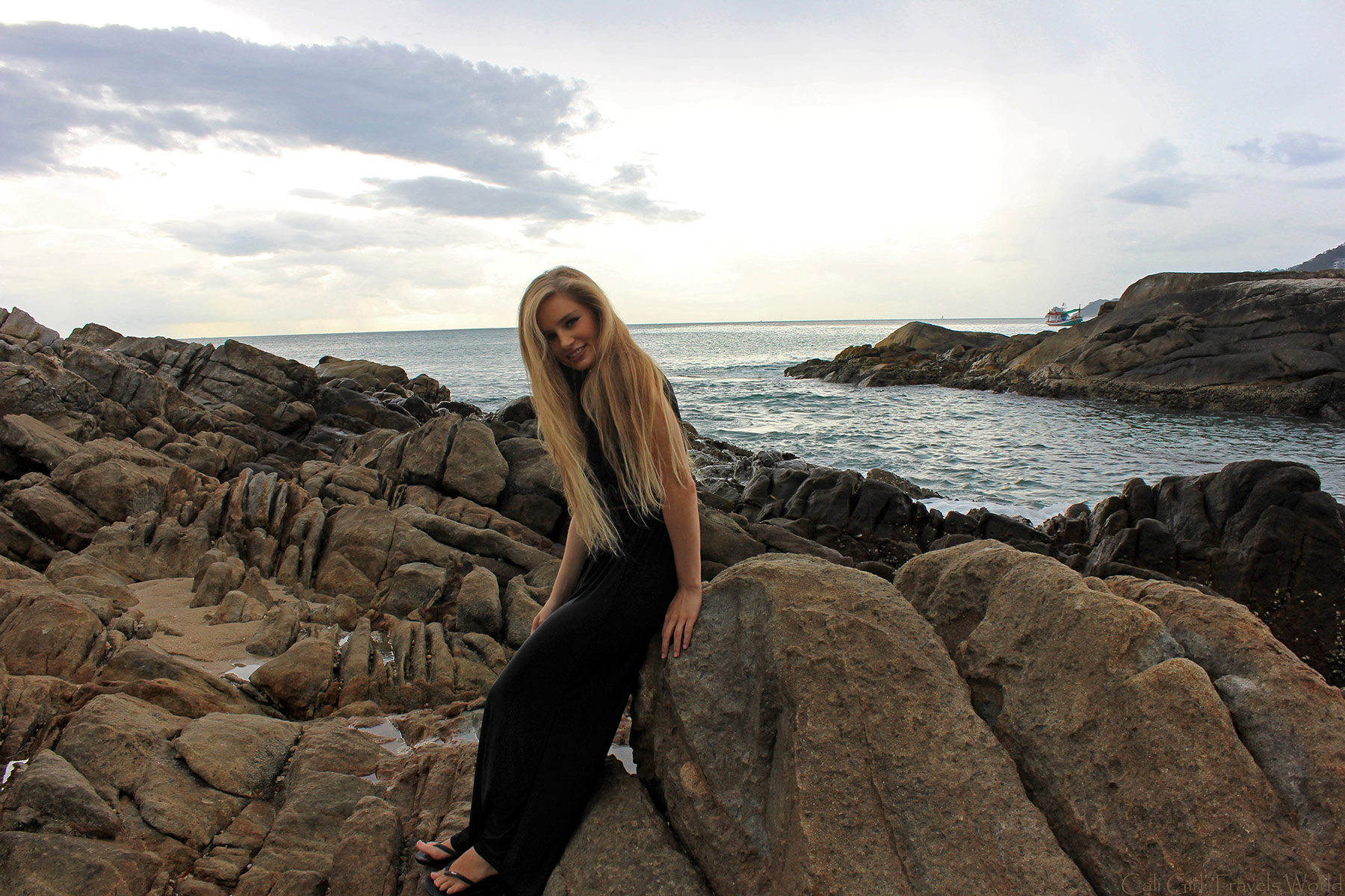 Blonde female travel blogger in long black dress at rocky beach smiling.