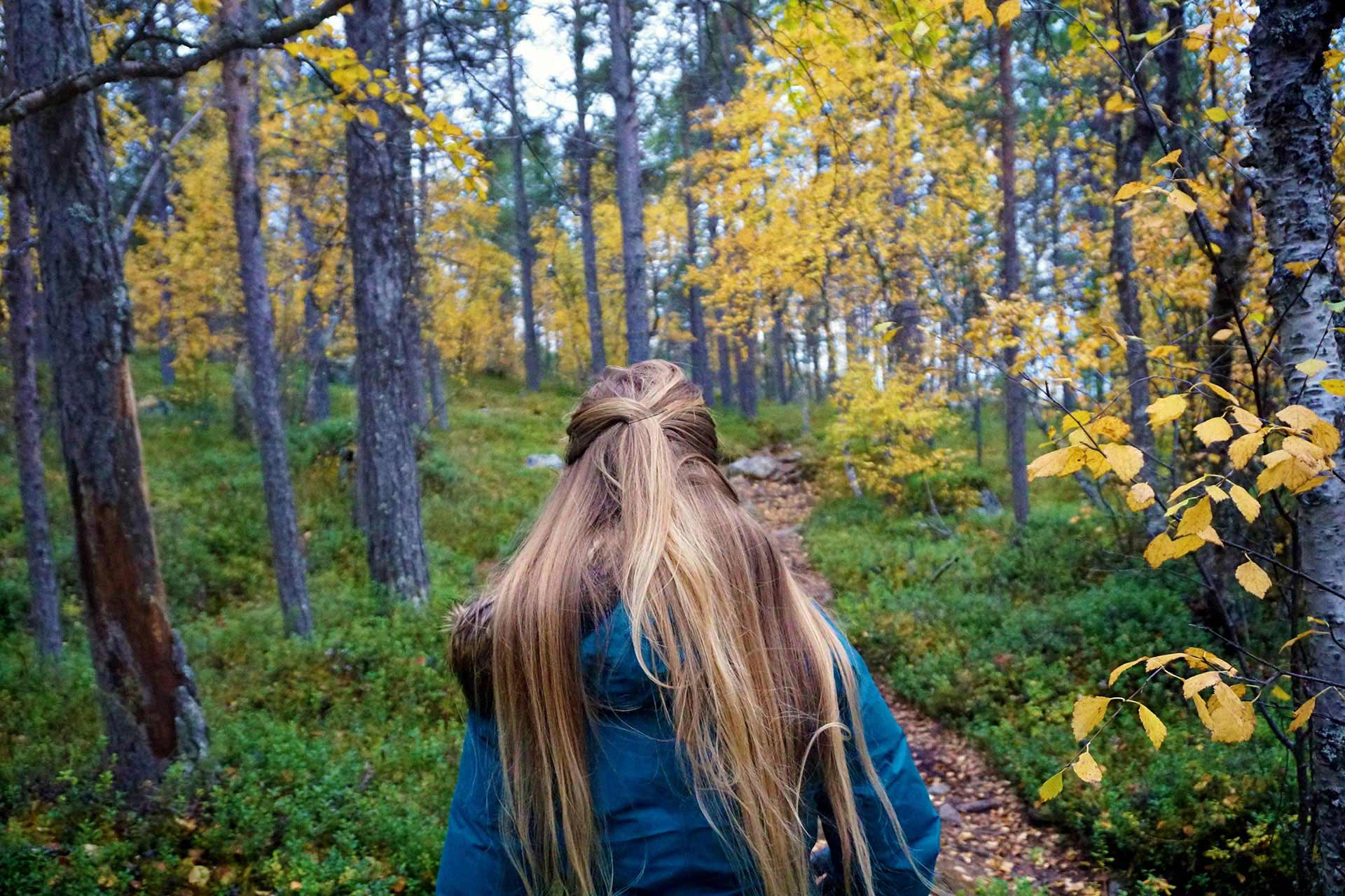 Cali Girl Travels World a travel blogger walking through along a path through Finnish nature in Inari, Lapland.