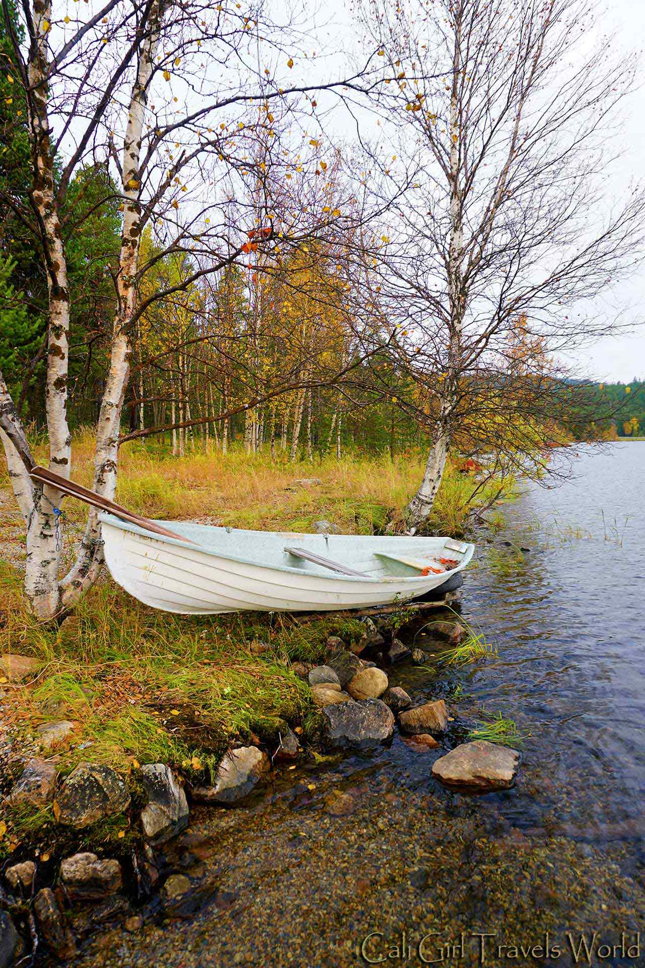 White row boat on the shore of a clear water lake in Lapland, Finland.