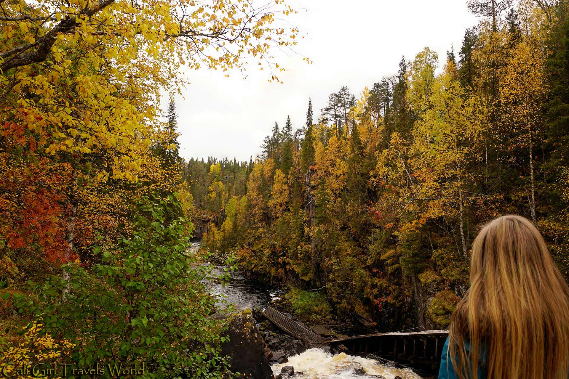 Travel blogger visiting Auttikongas river gorge near Rovaniemi, Finland in Lapland among ruska or autumn colors.