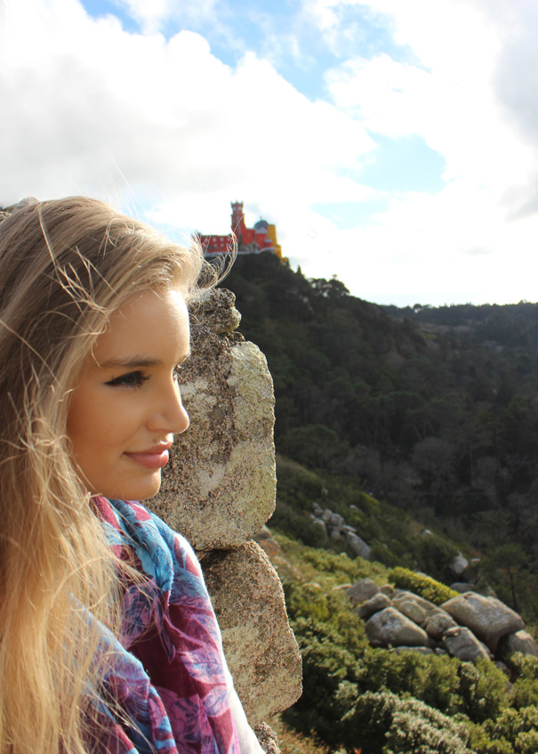 travel blogger looking out at Pena Palace in Sintra, Portugal.