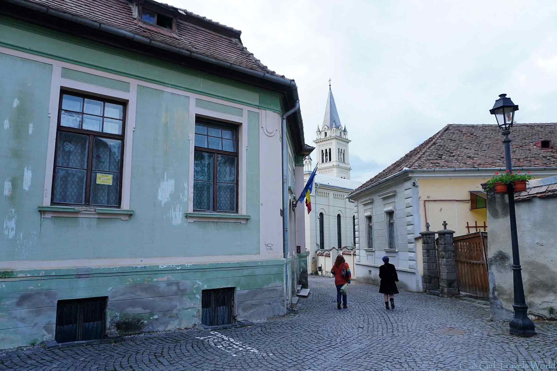Two women walking along a quaint medieval street in Sighisoara, Transylvania, Romania.