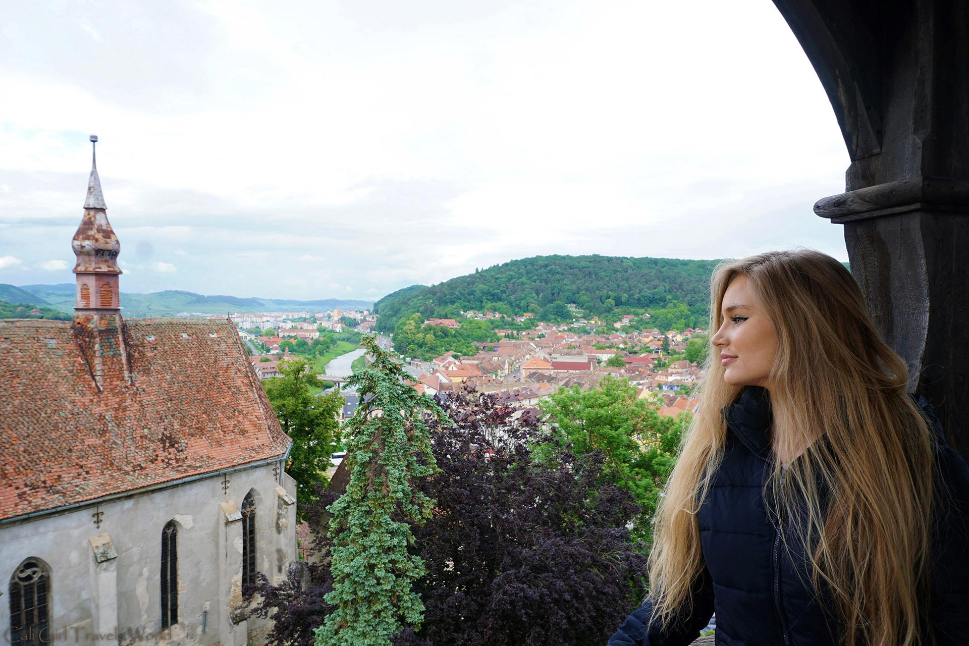 Female Travel Blogger looking out over the city with the council tower and churches of Sighisoara below.