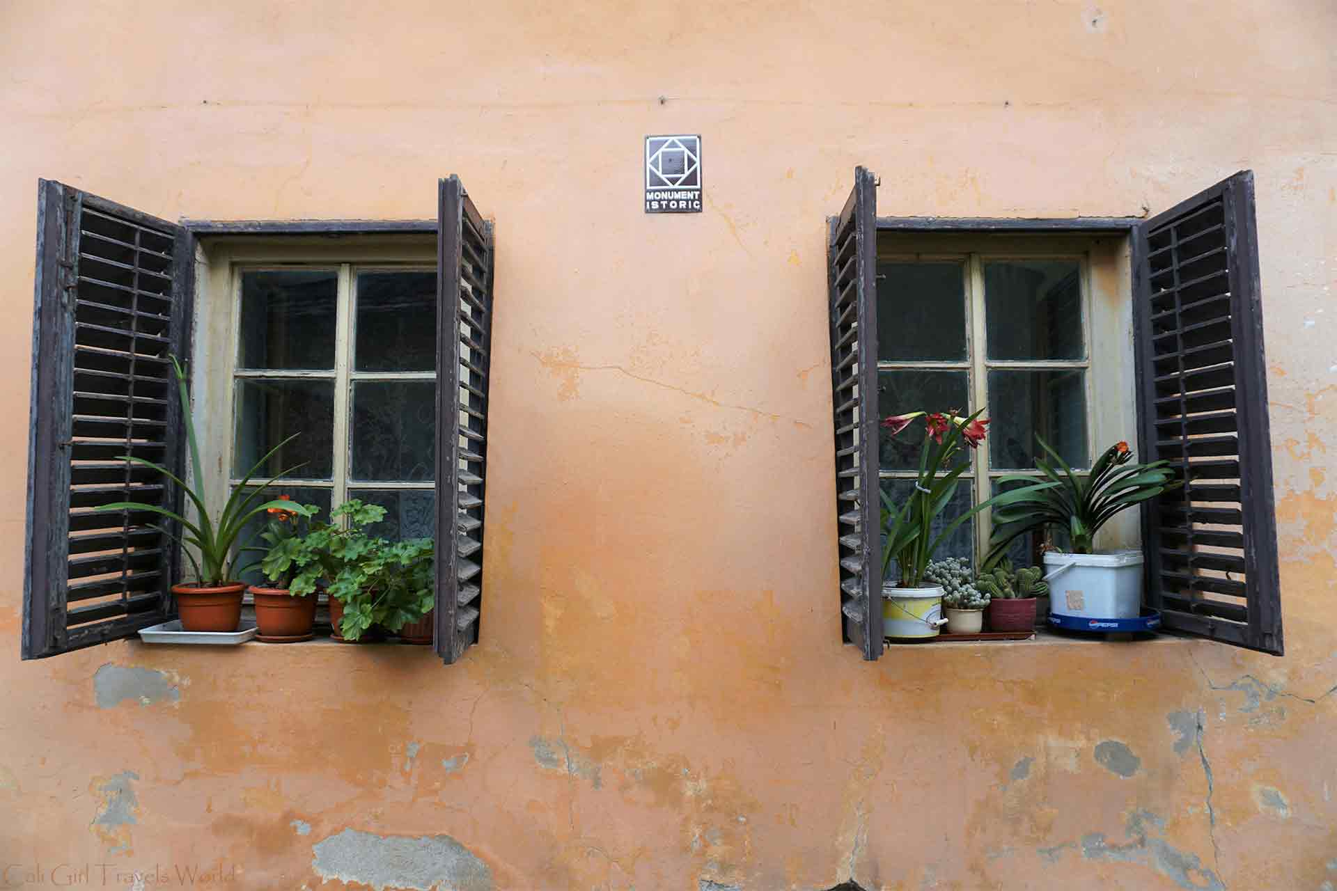A historic home in Sighisoara, Romania with their shutters open and flower pots in the window.