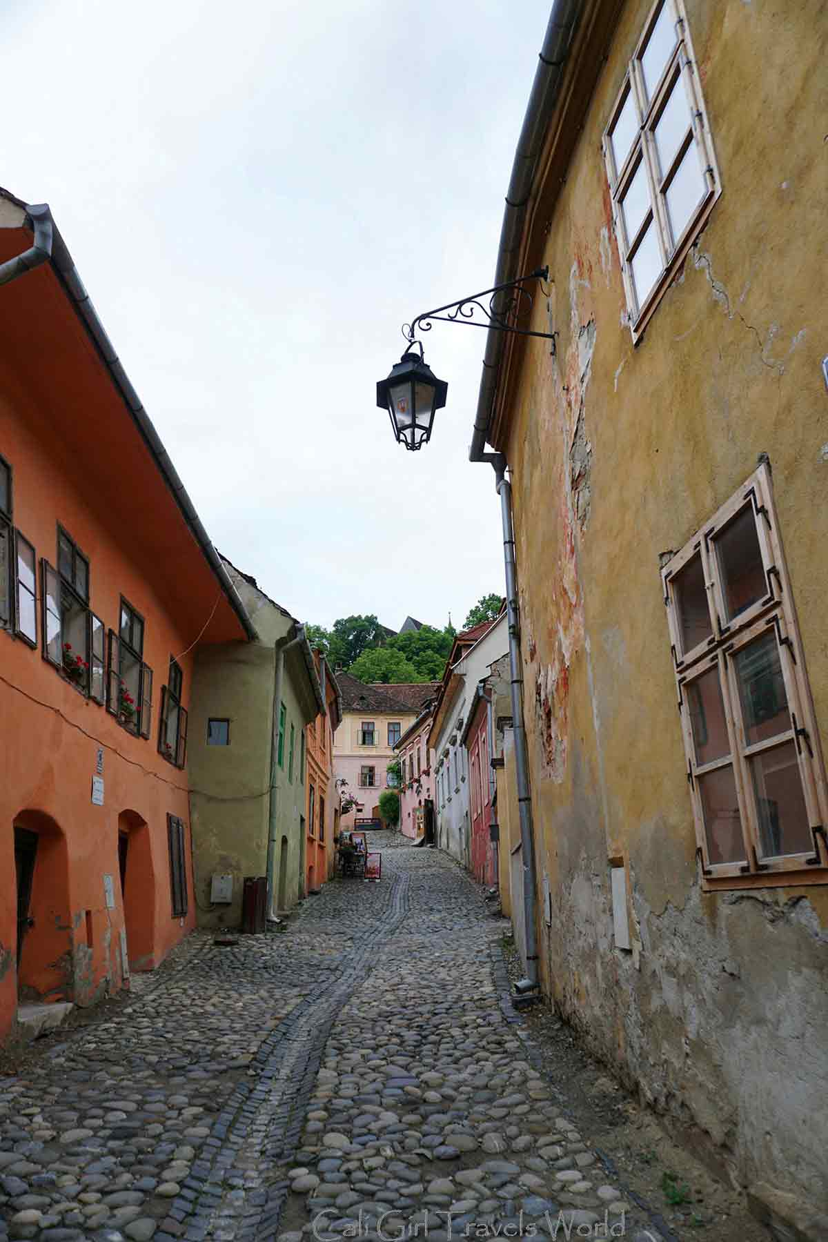 An uphill street lined with brightly colored house in Sighisoara, Translyvania, Romania.