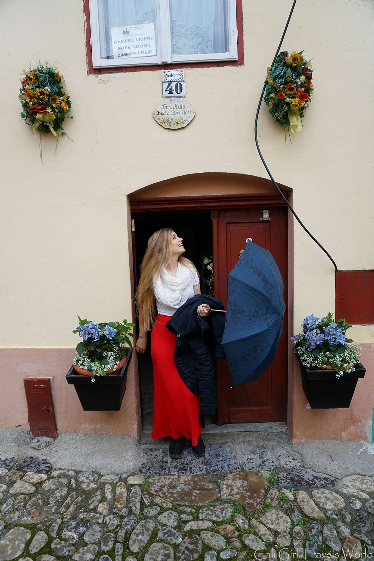 A female traveler in a tiny doorway of Sighisoara, Romania holding an umbrella.