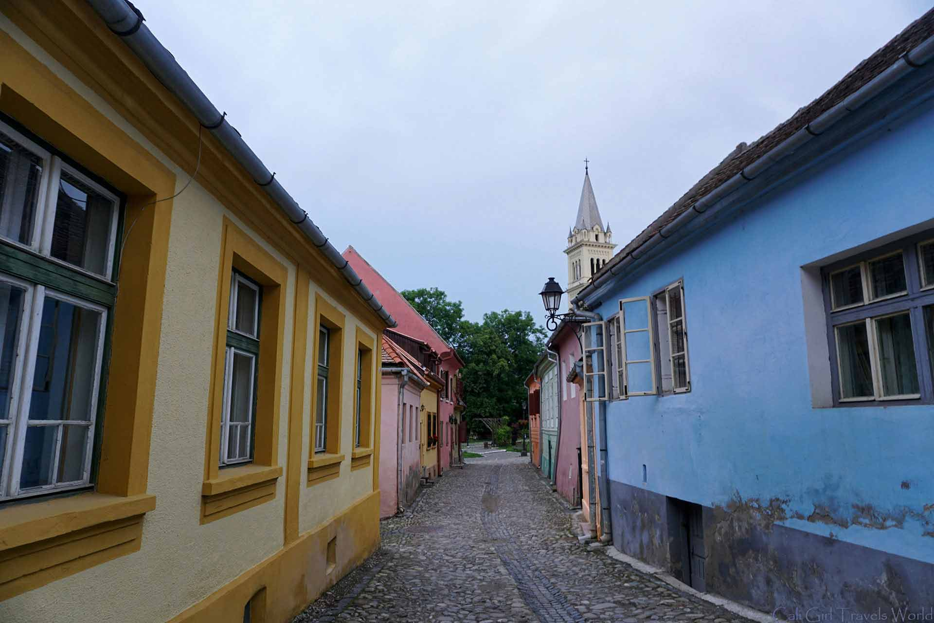 Colorful quaint street with a spire at the end.