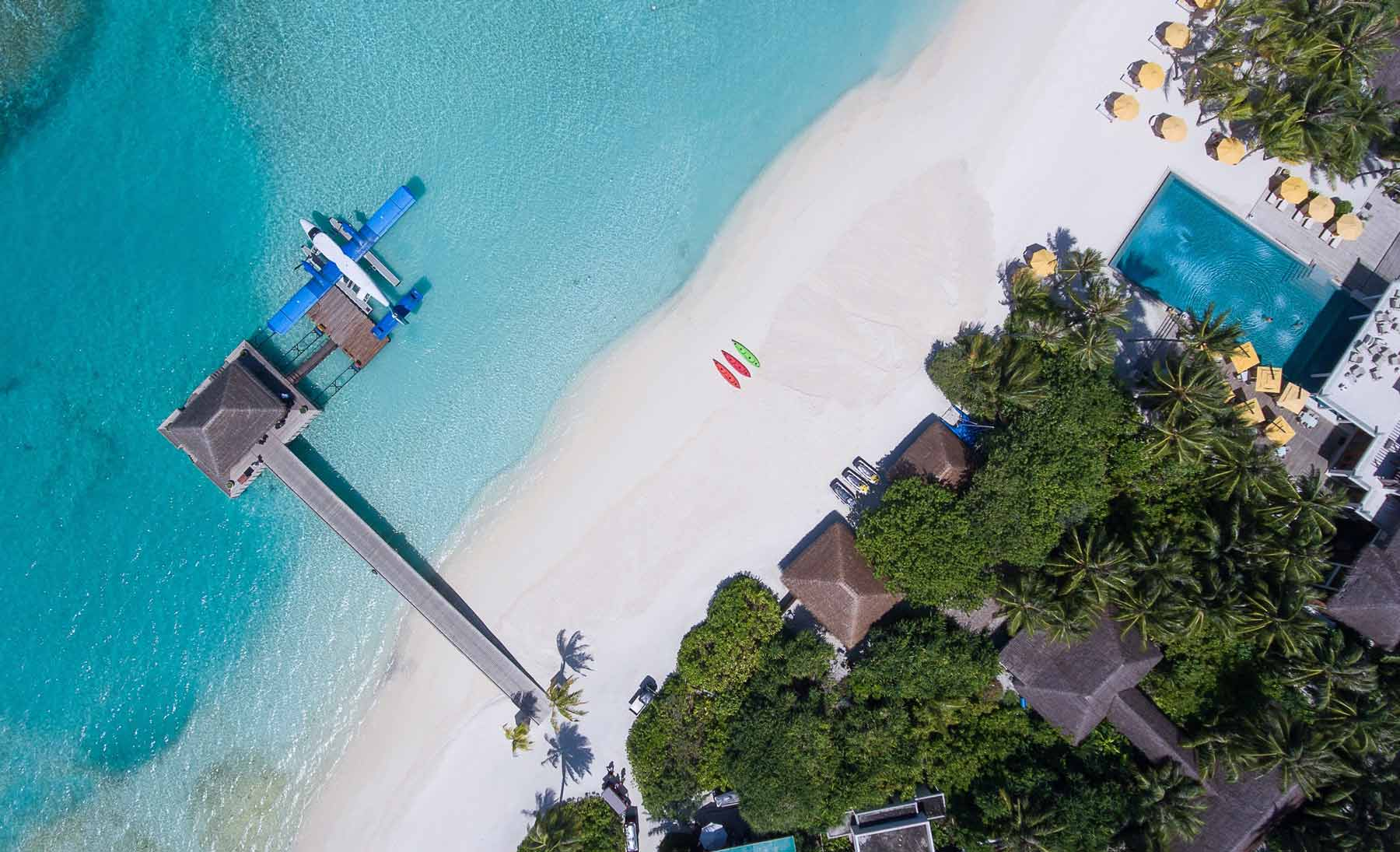 Small water plane on an island with white sand and bright blue clear waters.